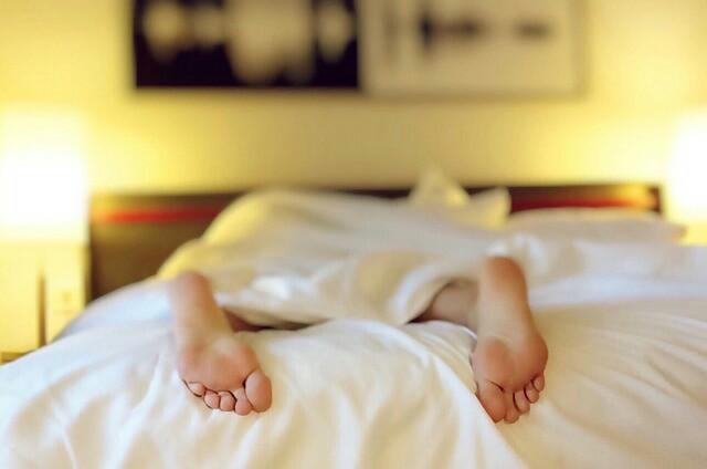 過労でベッドに倒れた人の足