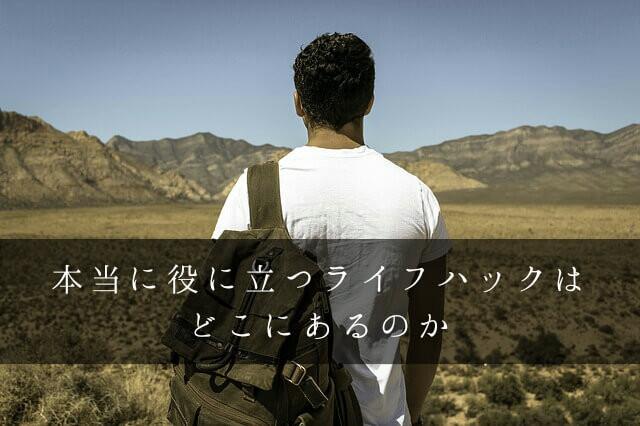 リュックを持って荒原を探検する男性の後ろ姿